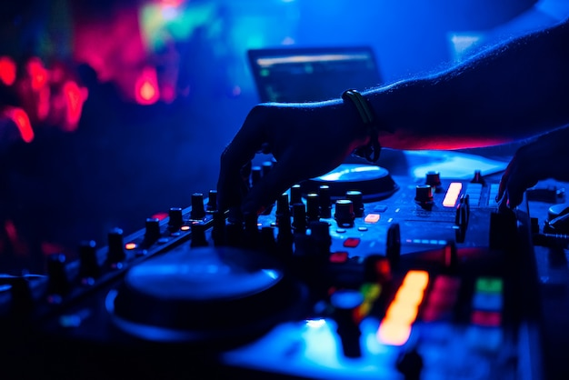 Dj die muziek mengen die de controlemechanismen op mixer in nachtclub bewegen
