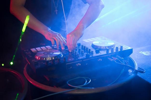 Dj draait draaitafelmuziek op nachtclubfeestje