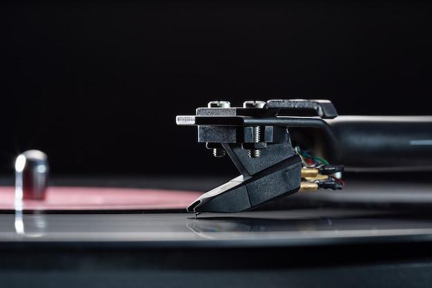 Dj-draaitafel voor vinylplaten, cartridge op toonarm en ruimte voor tekst.