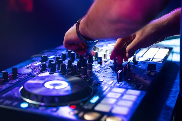 Dj handen mixen muziek op een mengbord in een nachtclub