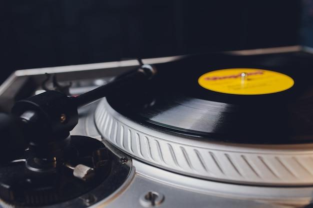 Dj handen op apparatuur dek en mixer met vinyl record op feestje.