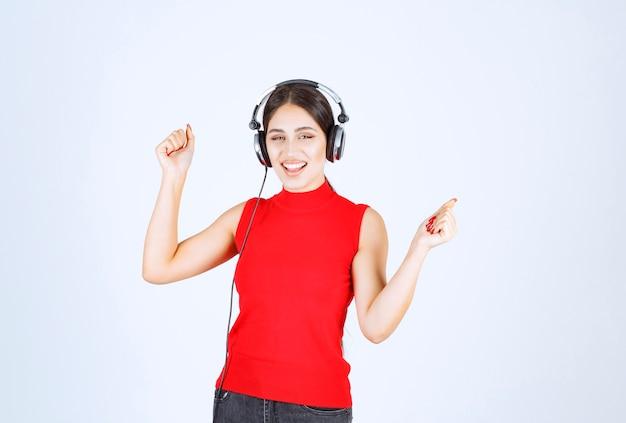 Dj in rood shirt met koptelefoon en genietend van de muziek.
