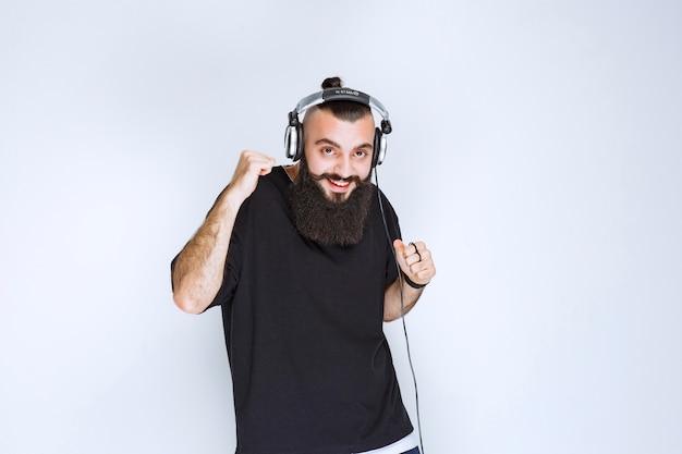 Dj met baard die een koptelefoon draagt die danst en zich actief voelt.