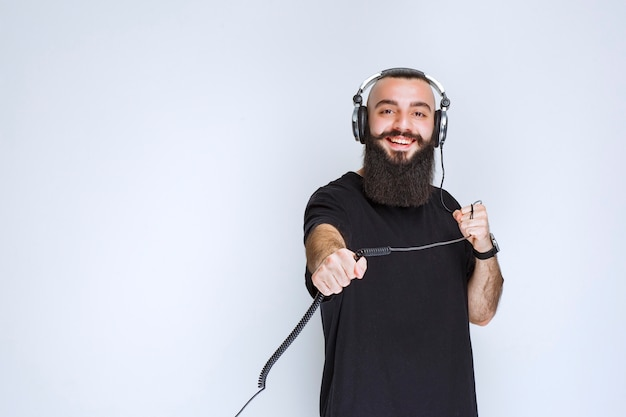 Dj met baard die een koptelefoon draagt en de kabel vasthoudt.