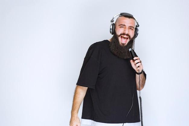 Dj met baard die een koptelefoon draagt en een karaoke zingt.