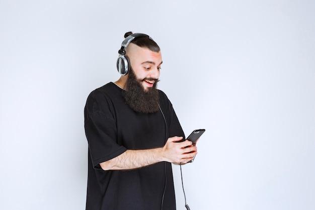 Dj met baard die een koptelefoon draagt en muziek van zijn afspeellijst op zijn smartphone zet.