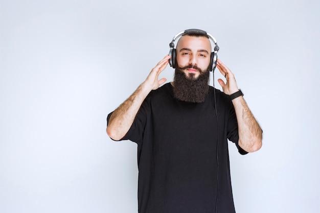 Dj met baard die een koptelefoon draagt en naar de muziek luistert.
