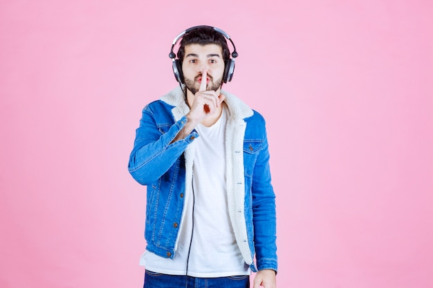 Dj met koptelefoon die om stilte vraagt