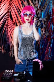 Dj met koptelefoon, roze haren en roze vinyl schijven