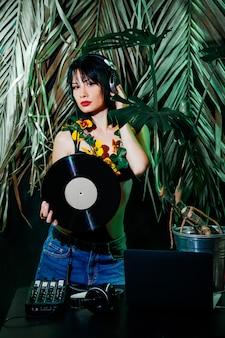 Dj met koptelefoon, zwart haar en vinyl schijf