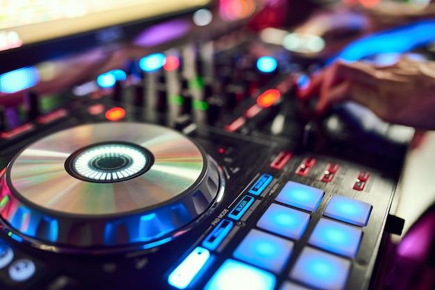 Dj mixt de track in de nachtclub op feest. op de achtergrond laserlichtshow