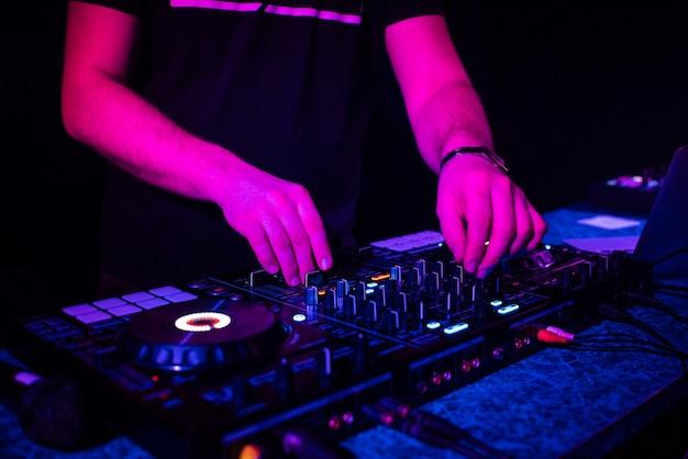 Dj mixt elektronische muziek met zijn handen op een muziekcontroller