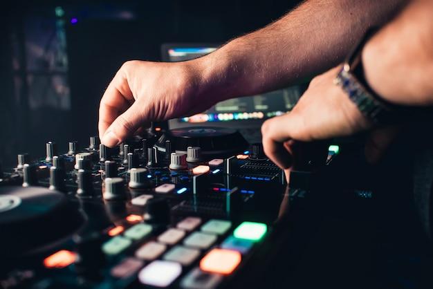 Dj mixt het nummer in nachtclub op feestelijke handen
