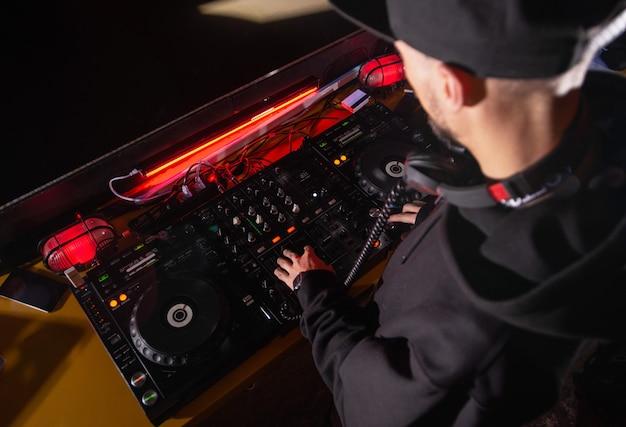 Dj mixt track op nachtclubfeest. bovenaanzicht van diskjockey in slimme vrijetijdskleding muziek afspelen op draaitafels. nachtleven concept. professionele muziekapparatuur.