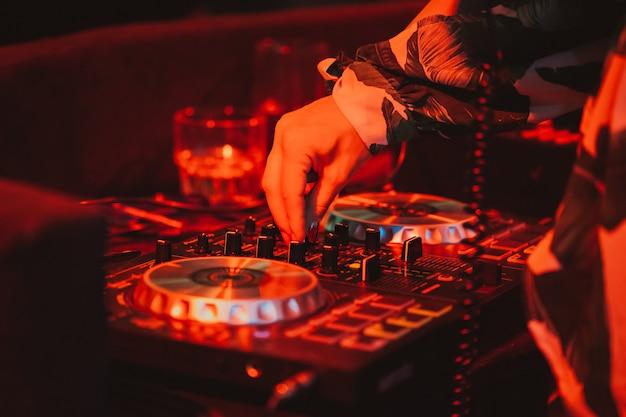 Dj op afstand op het podium in de nachtclub