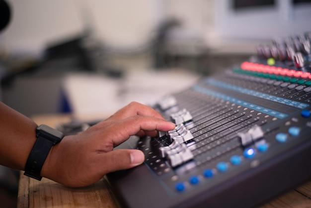 Dj past het volume van het geluid aan. professionele audio-mengtafel