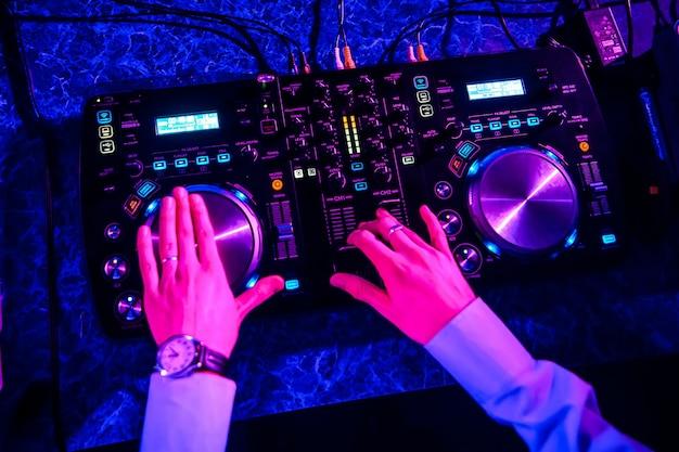Dj rijden muziek op professionele apparatuur in nachtclub