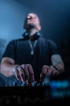 Dj-speelhuis en technomuziek in een nachtclub. muziek mixen en besturen.