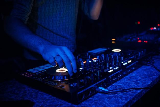 Dj speelt elektronische muziek in een nachtclub op een feestje