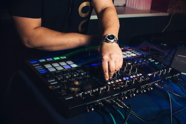 Dj speelt handen op professionele mixer bij nachtclub