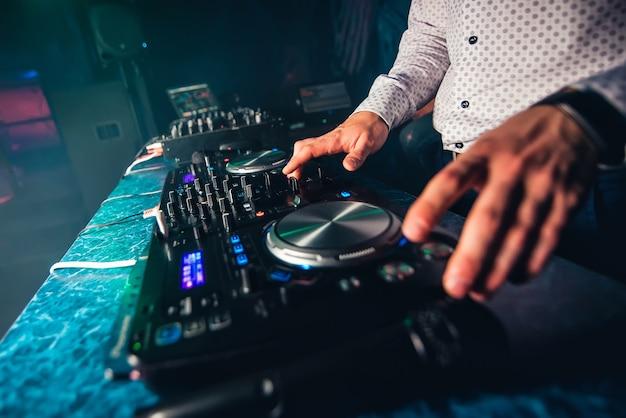 Dj speelt muziek in nachtclub op feestje door de knoppen en niveaus te bedienen