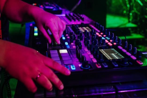 Dj speelt muziek op professionele mixer voor muziekapparatuur