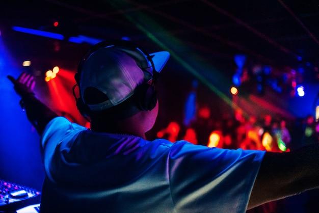 Dj vanaf de achterkant op het podium van een nachtclub met koptelefoon