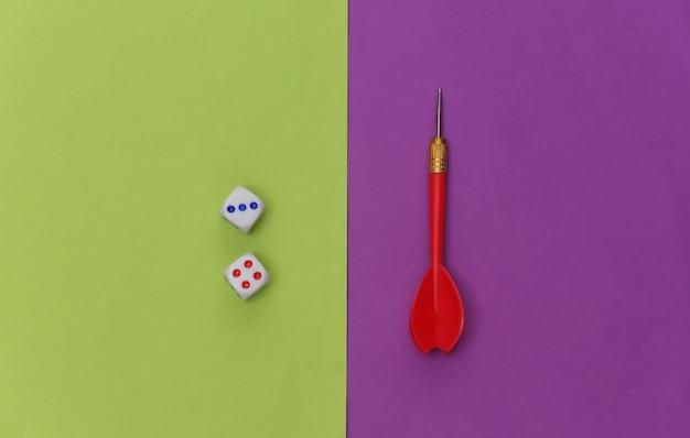 Dobbelstenen en darts op paars groene achtergrond. bovenaanzicht