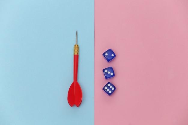 Dobbelstenen en darts op roze blauwe pastel achtergrond. bovenaanzicht