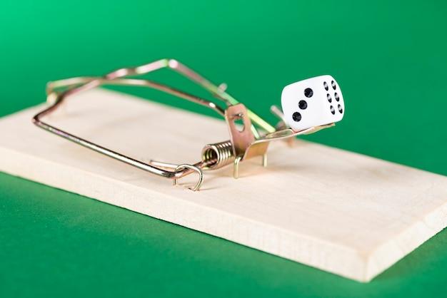 Dobbelstenen en muizenval, spelval, op een groene achtergrond, raken gokverslaving.