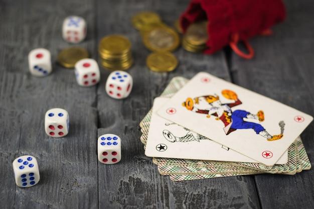 Dobbelstenen, munten en kaarten joker op een houten speeltafel.