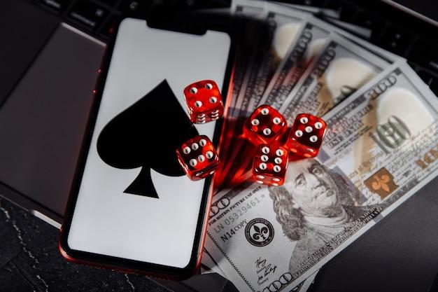 Dobbelstenen, smartphone en dollarbankbiljetten op toetsenbordclose-up. online casino concept.