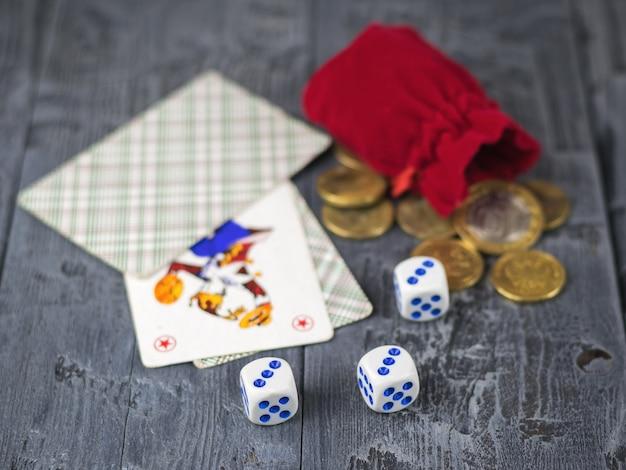 Dobbelstenen, speelkaarten en een rode geldzak op een houten tafel.
