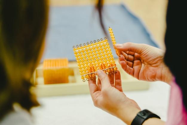 Docenten die wiskundekinderenstudenten tonen met behulp van montessoriemateriaal.