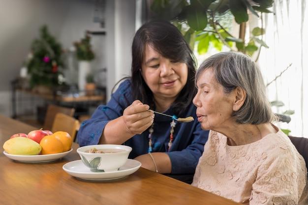 Dochter die bejaarde moeder met soep voedt.