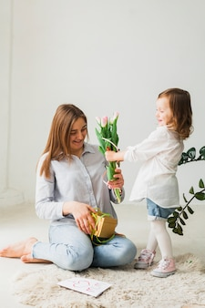 Dochter die bloemen geeft aan moeder met giftdoos
