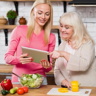 Dochter die digitale tablet en moeder het scrollen houden
