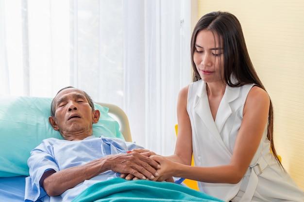 Dochter die en hogere mensenpatiënt in het ziekenhuis bezoeken troosten.