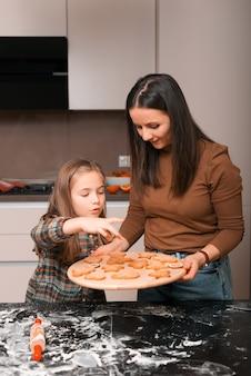 Dochter die enkel verse hete gebakken gemberbroodvormen bekijkt