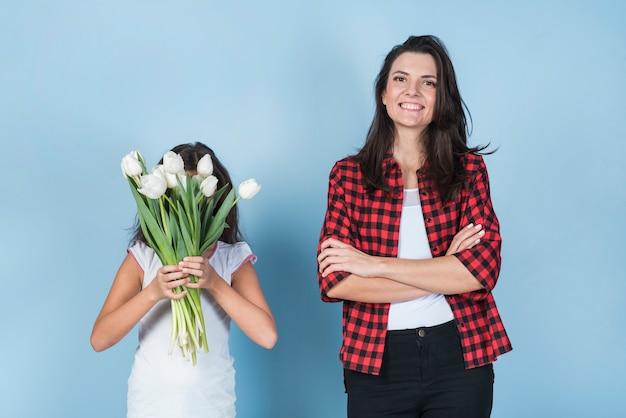 Dochter die gezicht behandelt met tulpen dichtbij moeder
