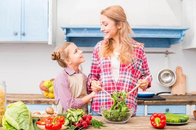 Dochter die haar moeder bekijkt die de salade in de keuken voorbereidt