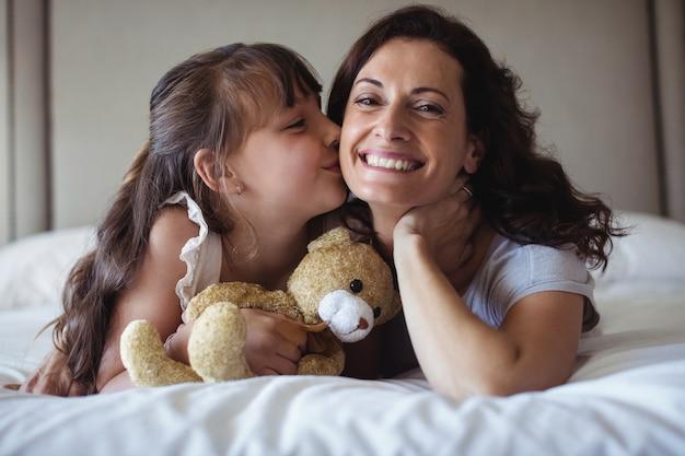 Dochter die haar moeder op wang in slaapkamer kust
