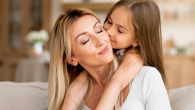 Dochter die haar moeder thuis kust