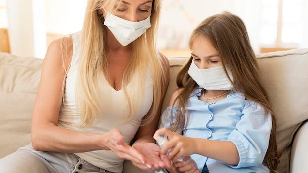 Dochter die handdesinfecterend middel geeft aan moeder