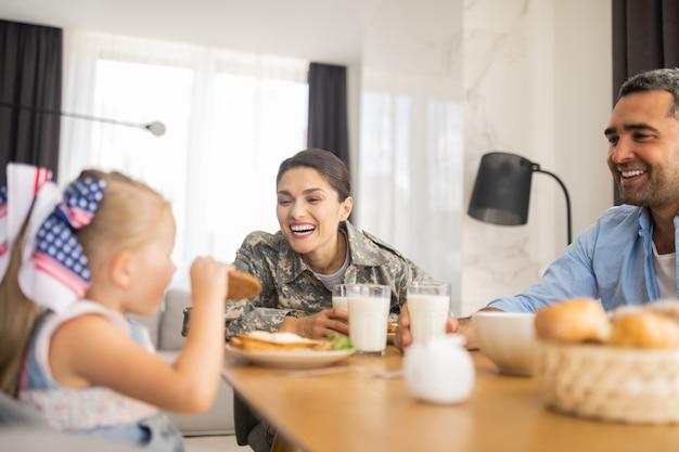 Dochter die koekje eet. aantrekkelijke gelukkige militaire vrouw die lacht terwijl ze naar haar dochter kijkt die een koekje eet