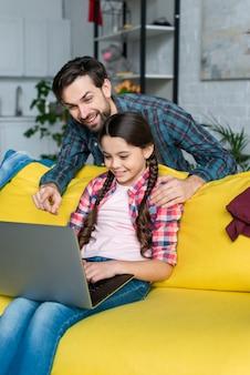 Dochter die laptop in woonkamer met behulp van