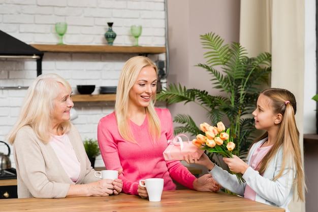 Dochter die moeder een boeket bloemen geeft