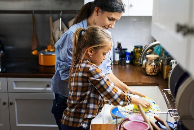 Dochter die moeder helpt bij het schoonmaken van schotels