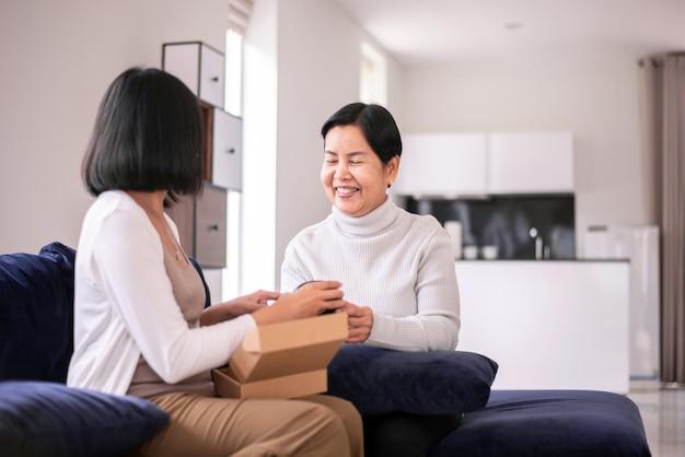 Dochter die moeder thuis een geschenkdoos geeft, gelukkig moederdagconcept