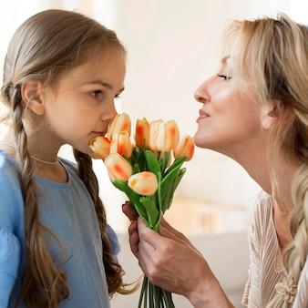 Dochter die moederboeket bloemen als cadeau geeft
